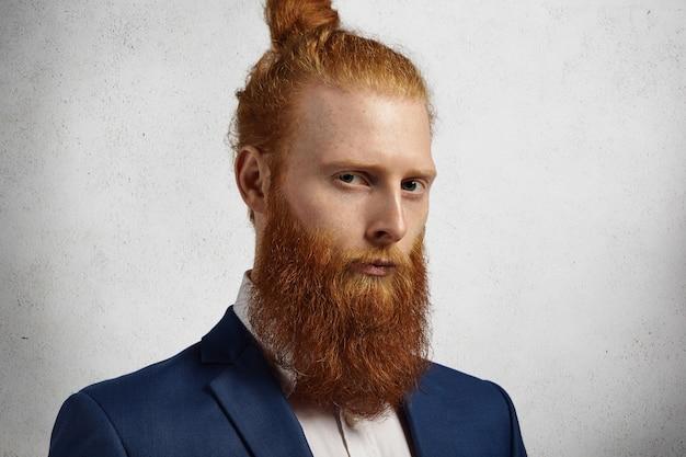 白い壁にオフィスに立っているファジーな赤いひげと髪の結び目と自信を持って起業家のヘッドショット。