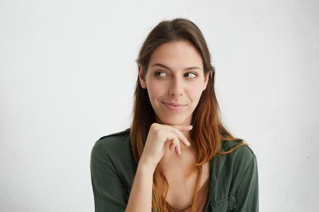あごの下で手を握ってよそ見ずる賢い美しい女性のヘッドショット。よそ見しながら陰険な表情を持つ魅力的な女性