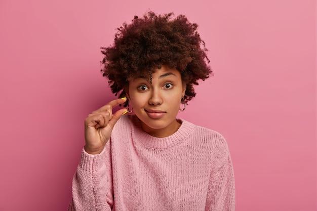 곱슬 머리 여자의 얼굴 사진은 매우 작은 것을 논의하고, 매우 작은 것을 형성하고, 입술을 지갑, 캐주얼 점퍼를 입고, 분홍색 벽에 절연, 작은 물체를 묻고, 작은 제스처를 만듭니다.