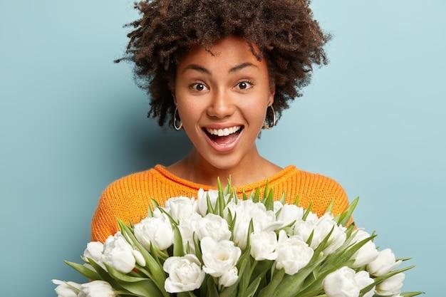 巻き毛の楽しい民族の女の子のヘッドショットは幸せに笑って、白い完璧な歯を示し、たくさんのチューリップを持って、夫から花を受け取って喜んで、カジュアルな服を着て、青い壁の上のモデル。