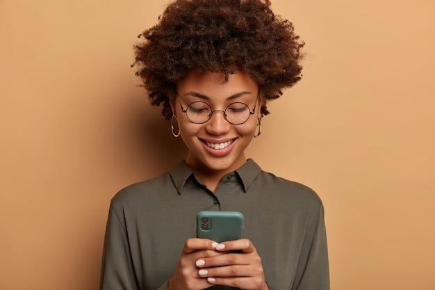 곱슬 머리 여자의 얼굴은 투명한 안경, 회색 셔츠를 입고 스마트 폰에서 무료 온라인 앱을 사용하고 이미지를보고 둥근 안경과 셔츠를 입습니다.
