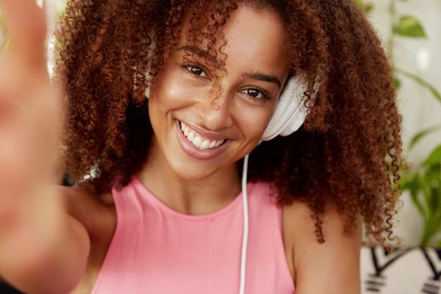 곱슬 머리를 가진 귀여운 젊은 여성의 얼굴 만은 헤드폰으로 음악을 듣고 소셜 네트워크에서 사진을 공유하는 동안 셀카를 만듭니다. 꽤 아프리카 계 미국인 여성 멜로 맨은 자신의 사진을 만든다