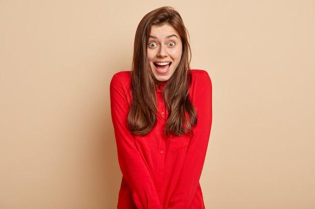 嬉しい表情で黒髪の若い白人女性の顔写真は、良い感情を表現し、ベージュの壁に隔離された赤いシャツを着て、歯を見せる笑顔を持っています。人、幸福と喜びの概念