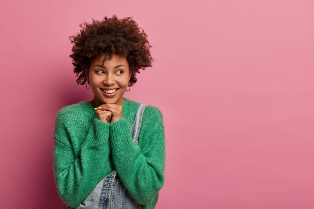 浅黒い肌の女性の顔写真は脇に見え、優しい笑顔を持ち、あごの下に手を保ちます