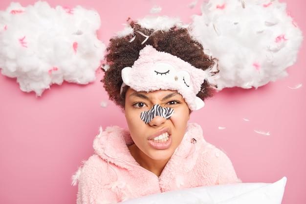 불쾌한 곱슬 머리 여자의 얼굴 만은 얼굴을 움켜 쥐고 이빨을 사용하여 주름을 줄이기 위해 코 패치를 적용하고 분홍색 벽 위에 절연 눈가리개와 잠옷을 착용합니다.