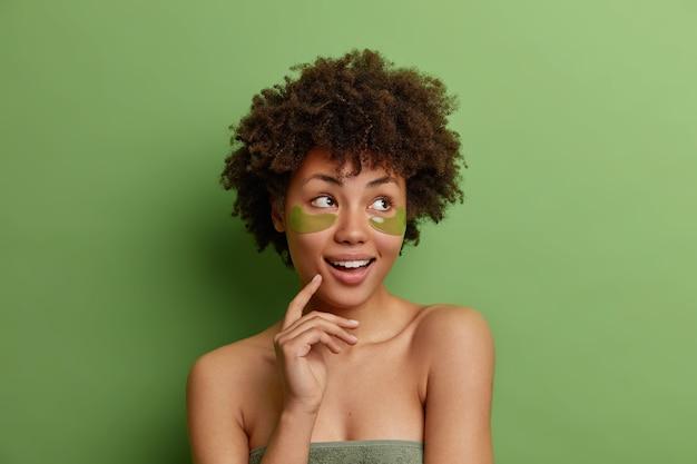 아프로 머리를 가진 꿈꾸는 사려 깊은 건강한 여성의 얼굴 만은 피부 관리 절차를 즐깁니다.