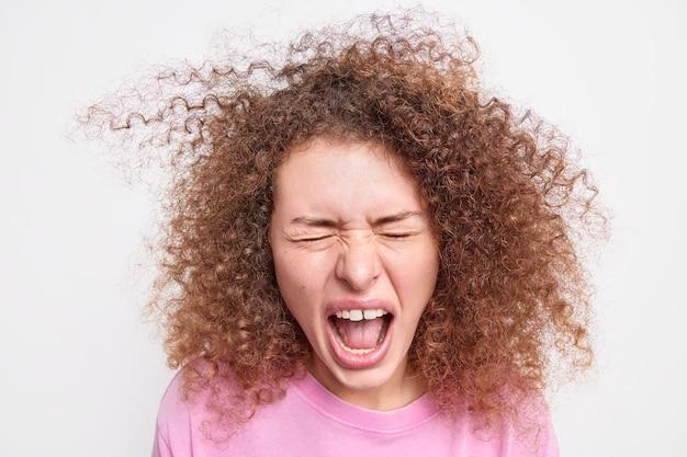 Выстрел в голову эмоциональной молодой кавказской женщины, громко кричащей с широко открытым ртом, с вьющимися густыми волосами, кричащими, что-то закрытыми глазами, изолированными над белой стеной. концепция людей и эмоций