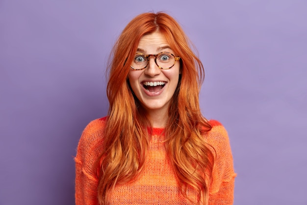 Выстрел в голову возбужденной рыжей европейской женщины с радостным выражением лица не может поверить, что ее успех носит очки и джемпер.