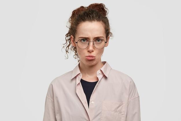 憂鬱な侮辱された若い女性のヘッドショットは、気分を害し、顔をしかめ、ボーイフレンドの悪い行動に不満を抱き、白い壁に隔離された特大のシャツを着た、くっきりとした黒髪をしています。