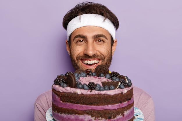 大きなおいしいフルーツケーキを受け取ってうれしいハンサムな無精ひげを生やした男のヘッドショット
