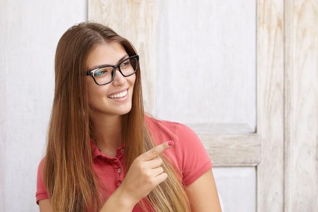 長方形のめがねで幸せな美しい女の子のヘッドショットは、白い歯を見せて、うれしそうで喜んでいる笑顔で探している人差し指をさりげなく指さして着飾った。ボディランゲージ。