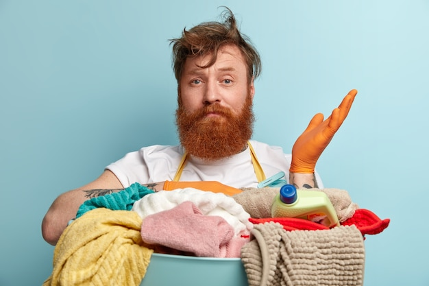 주저하는 빨간 머리 수염 난 남자의 얼굴 만 의심으로 손을 들어