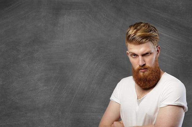 Выстрел в голову модного хипстерского мужчины с длинной рыжей бородой и стильной стрижкой, с сердитым и несчастным выражением лица, хмурым и хмурым, позирующим на пустой доске со скрещенными руками