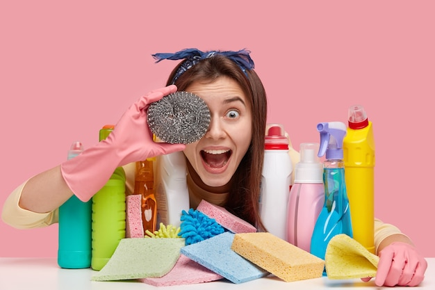Радостная женщина с прямыми темными волосами прикрывает глаза губкой, веселится после уборки комнаты, позирует за столом с химическими продуктами в разноцветных бутылках.