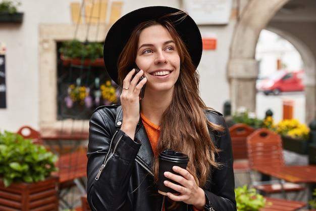 휴대 전화로 오랜 친구를 듣고 기뻐하는 사랑스러운 쾌활한 여성의 얼굴 사진, 해외 여행이 있습니다.