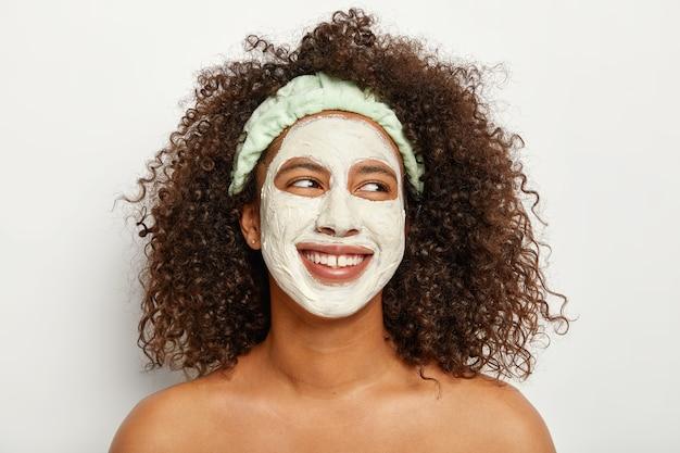 사랑스럽고 어두운 피부의 곱슬 머리 여성의 얼굴 사진은 상쾌한 피부를 위해 클레이 마스크를 적용하고 기꺼이 옆으로 보이며 매력적인 미소를 지으며 흰색 벽에 토플리스를 서 있습니다. 퍼스널 케어, 미용