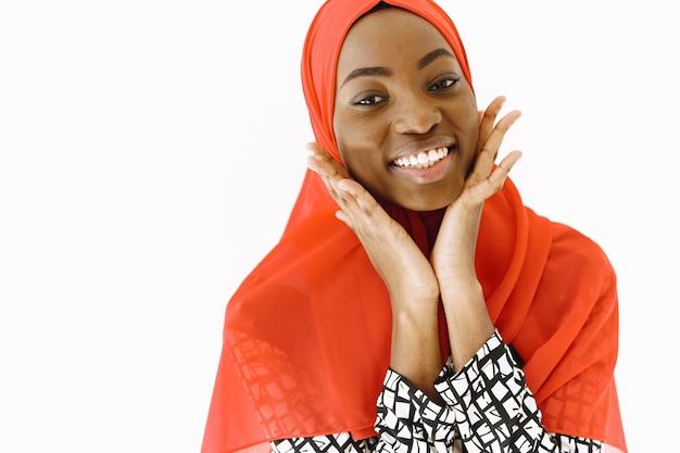 부드러운 미소, 어둡고 건강한 피부를 가진 사랑스러운 만족스러운 종교 무슬림 여성의 얼굴 사진은 머리에 스카프를 착용합니다. 흰색 배경 위에 격리.