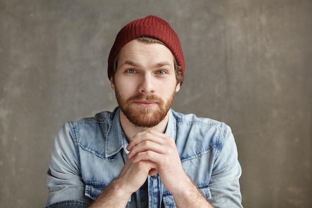 スタイリッシュな帽子と彼の前で握りしめられて手を繋いでいるブルージーンズシャツを着て、思慮深く夢のような表情で、コンクリートの壁に座っているモダンな見栄えの良い若いヨーロッパのヒップスターのヘッドショット
