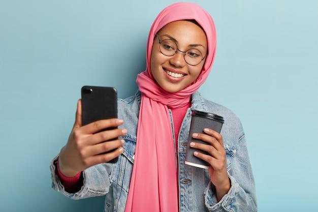 낙관적 인 쾌활한 여성의 얼굴 사진은 안경, 분홍색 베일을 착용하고 머리를 기울이고 스마트 폰의 카메라를 즐겁게 바라보고 테이크 아웃 커피를 마신다.