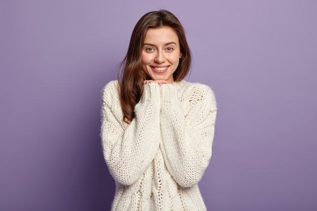 Выстрел в голову оптимистичной прекрасной женщины с прямыми волосами, держит руки под подбородком, носит белый свитер от счастья, позирует у фиолетовой стены концепция людей и эмоций