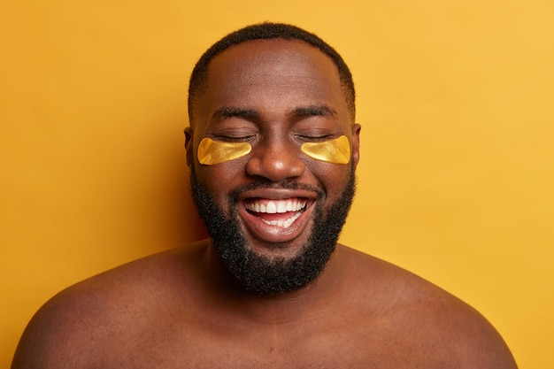 너무 기뻐서 어두운 피부를 가진 남성 모델의 얼굴 사진은 눈 밑에 황금색 패치를 착용하고 미용 및 위생 절차를 만듭니다.