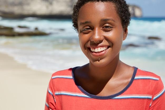 소년 같은 모습으로 즐거운 찾고 쾌활한 흑인 젊은 여성의 얼굴 만