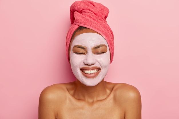 유쾌하고 어두운 피부를 가진 여자의 얼굴 사진은 얼굴에 진흙 마스크를 바르고, 맨 어깨에 서고, 미용 절차를 가지고, 눈을 감고 있습니다.