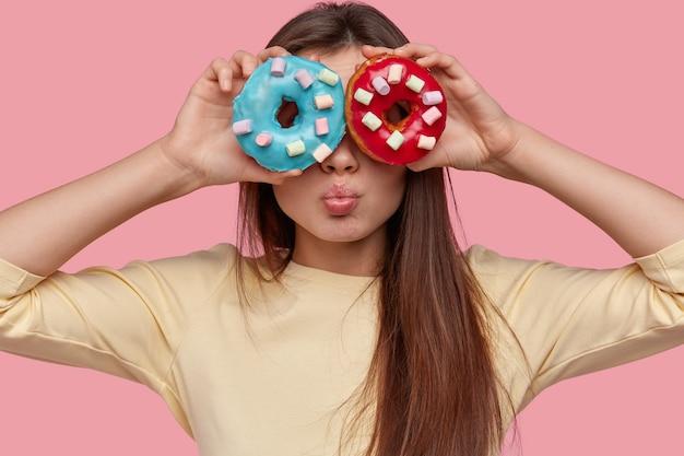 유쾌한 여성의 얼굴 사진은 두 개의 도넛으로 눈을 덮고, 긴 머리에 밝은 노란색 점퍼를 입고, 분홍색 스튜디오 벽 위에 모델