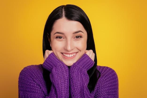 気持ちの良い見た目のフレンドリーなかわいい若い女性のヘッドショットは、積極的に笑顔、白い歯を示し、両手で顎を保持し、黄色の背景で隔離されます。人と良い感情の概念