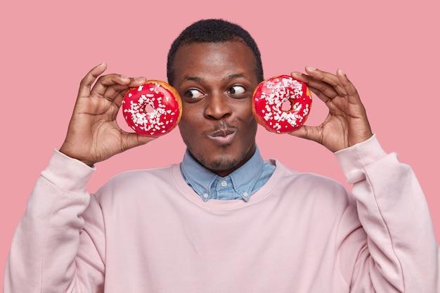 喜んでいる暗い肌の男性のヘッドショットは、ピンクの空間にモデルのフォーマルなシャツとセーターを着て、頭の近くに新鮮なドーナツを保ちます