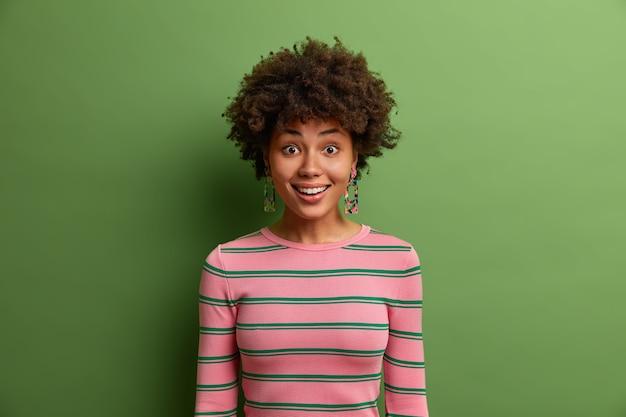 アフロの髪の幸せな笑顔の女性のヘッドショットは、嬉しそうに見え、陽気な気分を持ち、素晴らしいニュースを聞き、緑の壁に隔離されたカジュアルなストライプのジャンパーを着ています。感情の概念