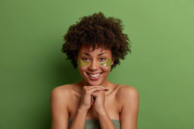 긍정적 인 어두운 피부를 가진 여성의 얼굴 사진은 아침 피부 관리 루틴을 즐기고, 눈 밑에 보습 마스크 패치를 적용하고, 피부를 관리하고, 상쾌한 행복한 표정을 지으며, 녹색 벽에 포즈를 취합니다.