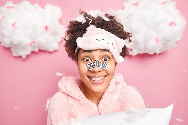 巻き毛のポジティブな女性のヘッドショットは目隠し鼻パッチ眠りのスーツを着ています驚くべきニュースがピンクの壁に隔離された枕を保持しているのを聞きます