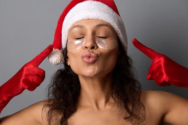 サンタの帽子をかぶったかなりブルネットの女性のヘッドショットは、彼女の顔の眼帯に指を向けています。クリスマスと新年の景品のための美容院の広告撮影。スパ、スキンケアのコンセプト