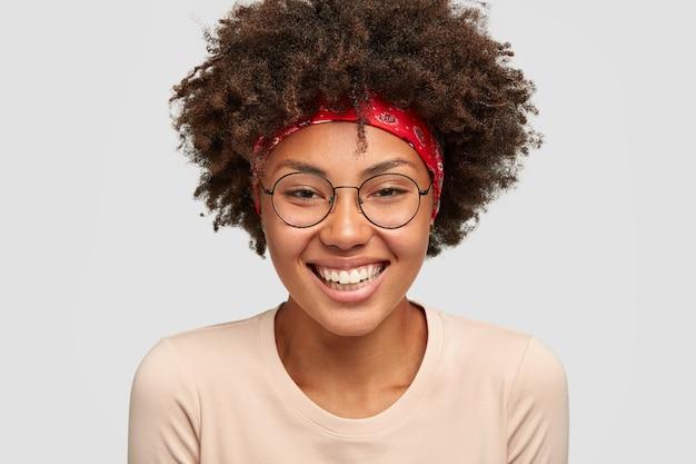 かなり暗い肌の女性のヘッドショットはふさふさした髪型をしています