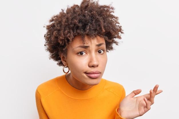 Выстрел в голову озадаченной афроамериканки выглядит с возмущенным выражением лица, внимательно слушает и пытается доказать, что у нее вьющиеся волосы, носит повседневный джемпер, позирует в помещении на фоне белой стены.