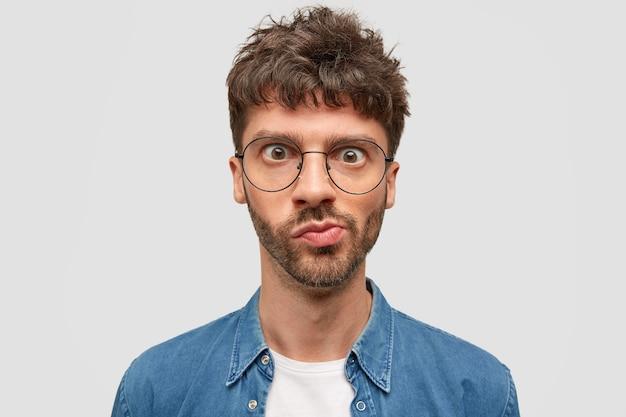 困惑したひげを生やした若い男のヘッドショットは、不思議に見え、唇を曲げ、目を大きく開いて、黒いウェーブのかかった髪をして、予期しないニュースを受け取り、何かについて考えます