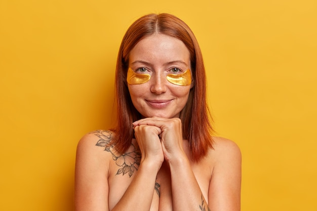밥 헤어 스타일을 가진 빨간 머리 여자의 얼굴 사진, 미용 절차를 즐기고, 콜라겐 황금 패치를 적용하고, 실내 알몸으로 서 있고, 피부와 외모에 관심이 있으며, 노란색 벽에 고립되어 있습니다.
