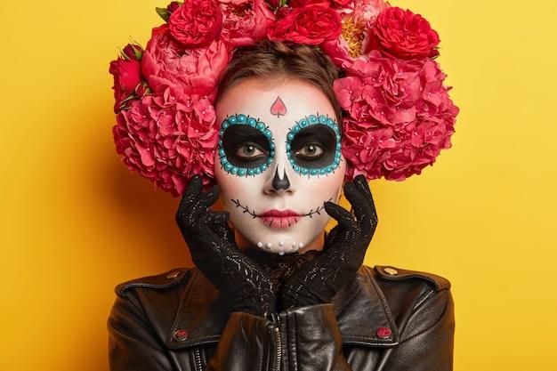 頭蓋骨の化粧をした真面目な美しい女性のヘッドショット、アーティストによって顔を描いた、黒い服を着て、不気味に見えたい、黄色の背景に対してポーズ。伝統的なメキシコの休日