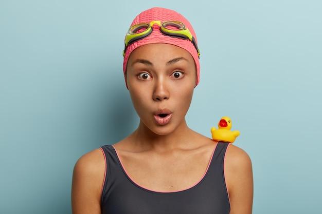 충격을받은 아프리카 계 미국인 여성의 얼굴 사진은 여름 휴식을 취하고 고글과 수영복을 착용합니다.