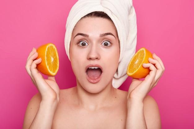 頭にタオルでショックを受けた美しい女性のヘッドショットは、顔の近くのオレンジスライスを保持し、あごを驚きから落とし続け、半分裸のポーズをとって、ピンクに分離しました。美容とスパのコンセプト
