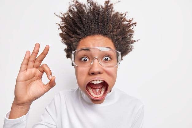 ショックを受けた感情的な縮れ毛の若い女性のヘッドショットは、あごを落とした上げられた髪を示しています大丈夫ジェスチャーはそれがクレイジーな外観を持っているのが好きだと言います