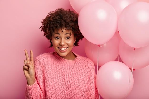 웃는 여성의 얼굴은 평화 제스처를 보여주고, 대형 니트 점퍼를 착용하고, 공기 풍선을 들고, 사진을 만들기 위해 포즈를 취하고, 장밋빛 벽 위에 고립 된 축제 행사를 축하합니다.