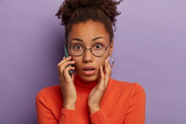 唖然とした感情的な暗い肌の女性のヘッドショットは、恐怖から息を呑み、不快なニュースを聞き、電話で会話し、光学ガラスとタートルネックを身に着け、紫色の背景の上にモデルを置きます。