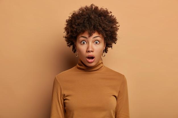アフロの髪をした唖然とした女性のヘッドショットは、何かを不思議に思って、興奮から息を呑み、口を開けたままにし、カジュアルなタートルネックに身を包み、ベージュの壁に隔離しました。とんでもない。真実である可能性は低い
