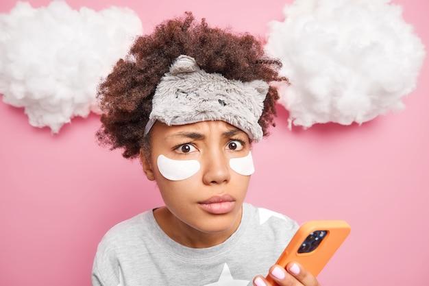 곱슬 머리를 가진 놀란 아프리카 계 미국인 여성의 얼굴 사진은 수면 마스크를 착용하고 잠자는 후 붓기를 줄이기 위해 눈 밑에 패치를 적용합니다. 파자마를 입은 뉴스 피드를 확인하기 위해 휴대 전화를 사용합니다.