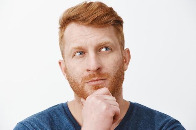 剛毛を持ち、あごに触れ、右上隅に焦点を合わせ、灰色の壁の上で正しい選択を選択しようと考え、決定を下す、思慮深い見栄えの良い戦略的な男性のヘッドショット
