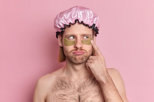 不幸な大人のヨーロッパ人男性のヘッドショットは、目の下に緑色のコラーゲンパッチを適用し、上半身裸のしわを減らします