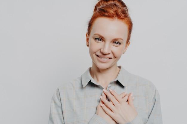 胸に手をつないで、愛と感謝を感じ、灰色のスタジオの背景に孤立してポーズをとっている間、素敵な赤い髪の白人女性に感謝している若い感謝の生姜のヘッドショット。ボディランゲージ