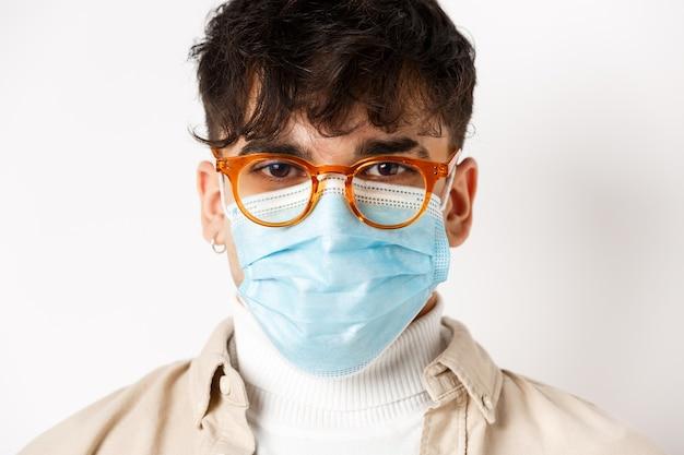 白い背景の上に立って、陽気でやる気に見える眼鏡と滅菌医療マスクの若い男のヘッドショット。社会距離拡大とコロナウイルスの概念